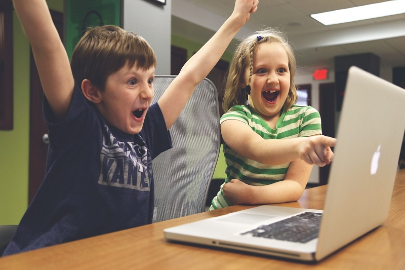 Children laughing in from of the computer