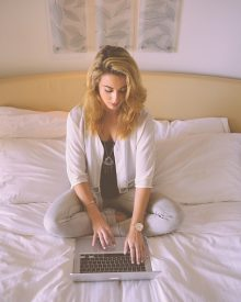 Female sitting on a bed with a computer